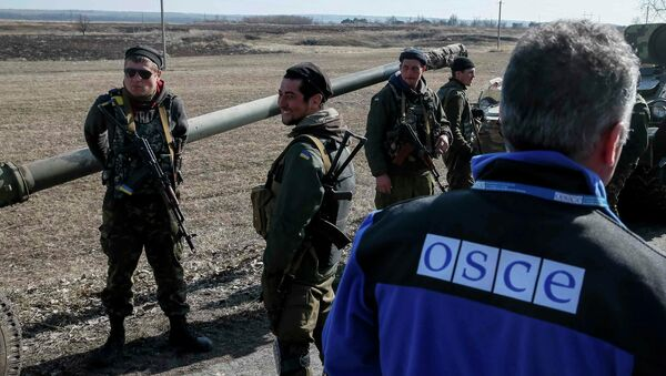 A member of Special Monitoring Mission of the OSCE to Ukraine walks along a convoy of Ukrainian armed forces in Blagodatne, eastern Ukraine, February 27, 2015 - Sputnik Italia