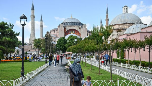 People walk in front of Hagia Sophia on July 11, 2020 in Istanbul, a day after a top Turkish court revoked the sixth-century Hagia Sophia's status as a museum, clearing the way for it to be turned back into a mosque. - Sputnik Italia