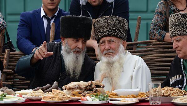 Gli anziani al tavolo durante un'esibizione di un gruppo folcloristico alla celebrazione della Giornata della città a Grozny - Sputnik Italia