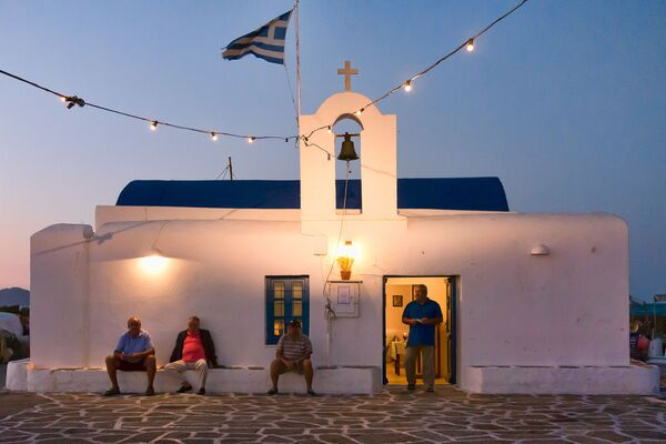 Dei pescatori davanti a una chiesa nel porto di Naoussa, Grecia. - Sputnik Italia