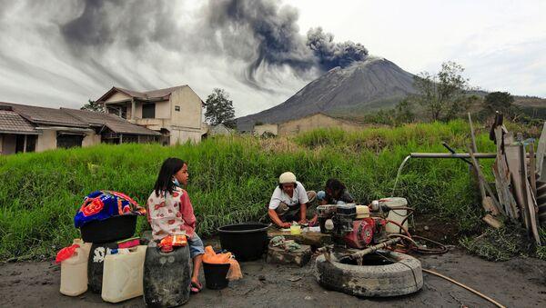 Люди стирают одежду у активного вулкана Синабунг, Индонезия  - Sputnik Italia