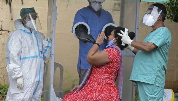 Забор мазка у женщины в бесплатном центре тестирования на коронавирус COVID-19 в Хайдарабаде, Индия - Sputnik Italia