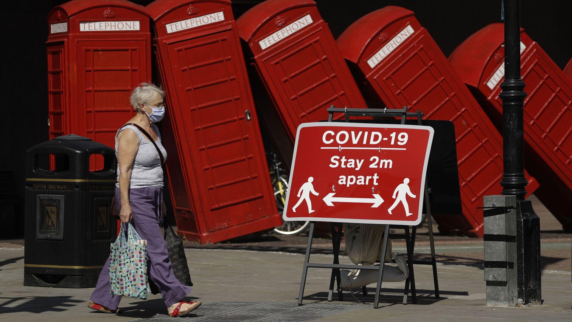 Женщина в медицинской маске и плакат с призывом соблюдать социальную дистанцию на фоне скульптуры британского скульптора Дэвида Маха Out of Order в Лондоне, Великобритания  - Sputnik Italia, 1920, 29.05.2021