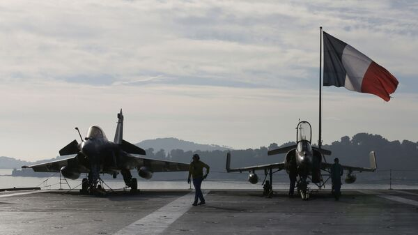 Flight deck crew work around a Rafale (L) and a Super Etendard fighter jets as a French flag flies aboard the French nuclear-powered aircraft carrier Charles de Gaulle before its departure from the naval base of Toulon, France, November 18, 2015 - Sputnik Italia