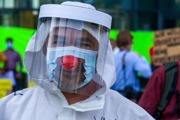 Un uomo indossa una maschera tagliata con un naso da clown e una visiera protettiva mentre partecipa a una manifestazione organizzata dall'associazione belga Folie Virale / Viruswaanzin contro le misure sanitarie adottate dal Belgio per combattere la pandemia di Covid-19 e chiedere le dimissioni di virologo Van Ranst, il 16 agosto 2020 a Bruxelles - Sputnik Italia