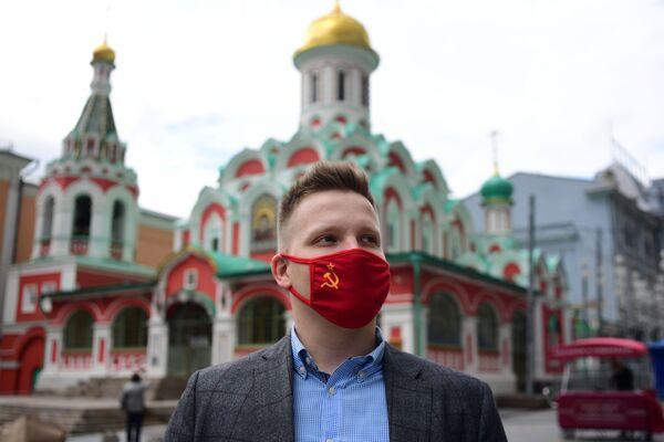 Un uomo con una mascherina protettiva con il simbolo dell'URSS a Mosca, Russia - Sputnik Italia