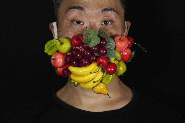 Edmond Kok, costumista e attore teatrale di Hong Kong, che indossa una maschera per il viso decorata con molti frutti diversi a Hong Kong giovedì 6 agosto 2020 - Sputnik Italia