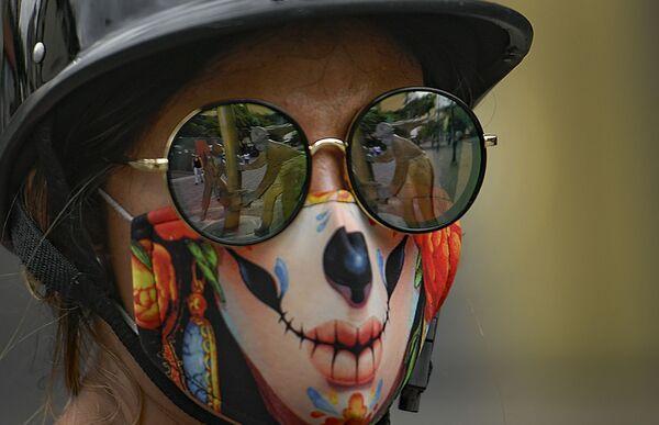 Una ragazza con occhiali da sole e una mascherina protettiva creativa contro il coronavirus a Caracas, in Venezuela - Sputnik Italia
