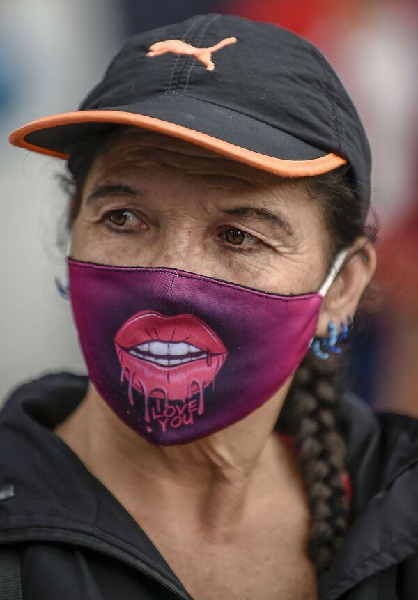 Una donna indossa una maschera per il viso come misura preventiva contro la diffusione del nuovo coronavirus COVID-19, durante una protesta contro il presidente colombiano Ivan Duque e il presunto stupro di ragazze indigene da parte di membri dell'esercito colombiano, a Bogotà il 10 luglio 2020 - Sputnik Italia