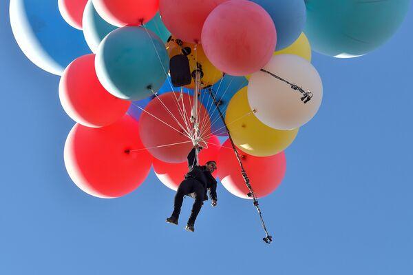Incredibile impresa, quella dell'llusionista David Blaine che aggrappato a 52 palloni pieni di elio, ha sorvolato raggiungendo circa i 7mila metri di altitudine, il deserto dell'Arizona, il 2 settembre 2020 - Sputnik Italia
