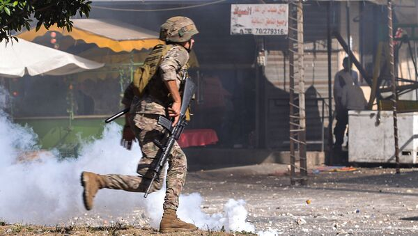 Un soldato libanese corre tra scontri con manifestanti antigovernativi nel quartiere di Bab al-Tabbaneh nella città portuale settentrionale di Tripoli, il 13 giugno 2020, il terzo giorno consecutivo di manifestazioni rabbiose in tutto il paese a causa di una crisi economica sempre più profonda - Sputnik Italia