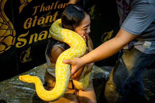 Un visitatore posa per una fotografia con un pitone durante il Pet Expo Thailand 2020 a Bangkok, il 5 settembre 2020 - Sputnik Italia