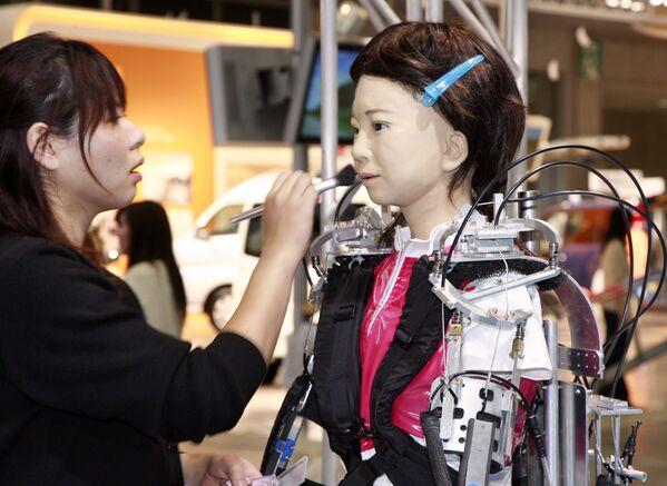 Una truccatrice applica il trucco a un robot umanoide di nome Pikarin alla mostra sull'assistenza domiciliare e la riabilitazione a Tokyo, il 3 ottobre 2007 - Sputnik Italia