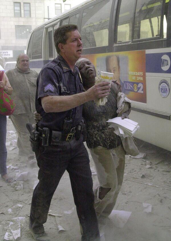 Agente di polizia con una vittima durante l'attacco terroristico dell'11 settembre 2001, USA - Sputnik Italia