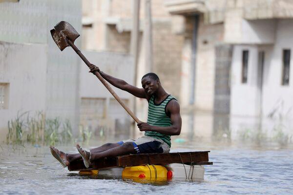 Uomo su un travamento improvvisato naviga sulle strade inondate dopo le piogge in Senigallia. - Sputnik Italia