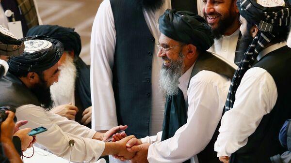 I delegati talebani si stringono la mano durante i colloqui tra il governo afghano e gli insorti talebani a Doha, in Qatar, 12 settembre 2020 - Sputnik Italia