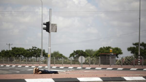 An Israeli woman takes cover as siren alarming sounds warning of rocket attacks by Palestinians militants from Gaza Strip in Ashkelon, southern Israel, Monday, July 14, 2014. - Sputnik Italia