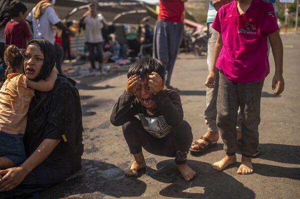 Un ragazzo migrante dopo che la polizia ha lanciato gas lacrimogeni durante gli scontri nei pressi della città di Mitilene, sull'isola greca di Lesbo, il 12 settembre 2020, pochi giorni dopo che un incendio ha distrutto il campo profughi di Moria - Sputnik Italia