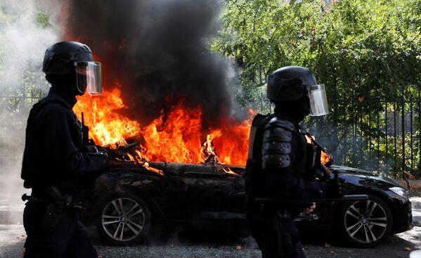 Gli agenti di polizia antisommossa francesi passano davanti a un'auto in fiamme durante una dimostrazione del movimento dei gilet gialli a Parigi, Francia, il 12 settembre 2020 - Sputnik Italia