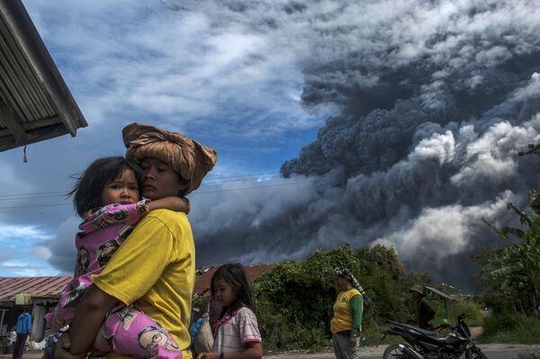 I residenti di un villaggio ai piedi del vulcano attivo Sinabung nel nord di Sumatra, in Indonesia - Sputnik Italia