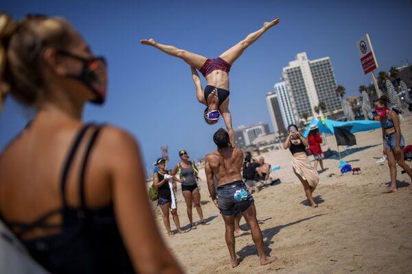 Gli acrobati si esibiscono durante una protesta contro la decisione del governo di chiudere le spiagge a causa della pandemia di coronavirus a Tel Aviv, Israele - Sputnik Italia
