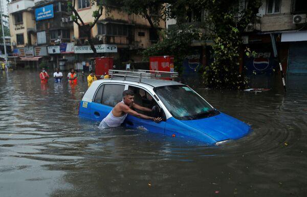 Un uomo spinge un taxi lungo una strada inondata dopo un temporale a Mumbai, in India - Sputnik Italia