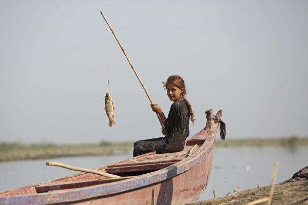 Una ragazza sta pescando vicino alla città Basra, Iraq - Sputnik Italia