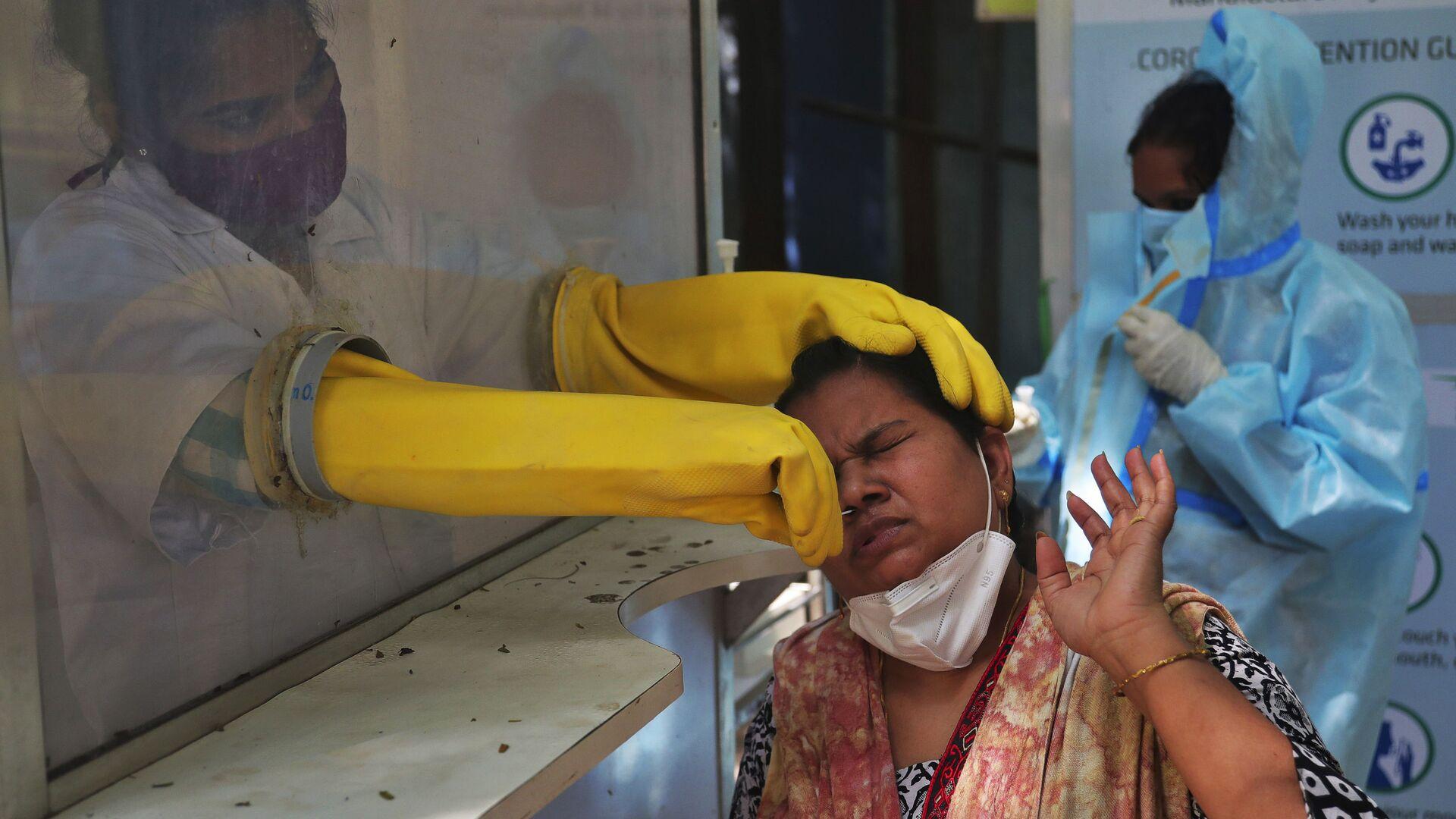 Медицинский работник проводит тест в Индии - Sputnik Italia, 1920, 20.05.2021