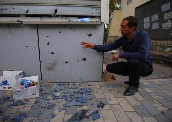 Un uomo fa vedere le distruzioni dopo i bombardamenti nella città Terter - Sputnik Italia