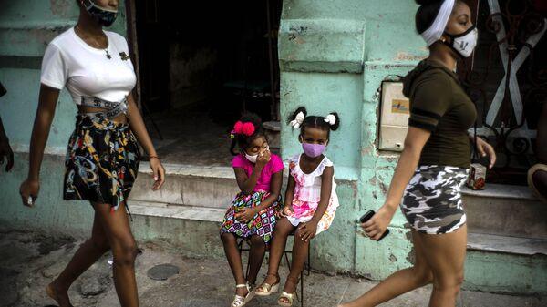 Девочки в масках ждут своих родителей, сидя на стуле в Гаване, Куба - Sputnik Italia