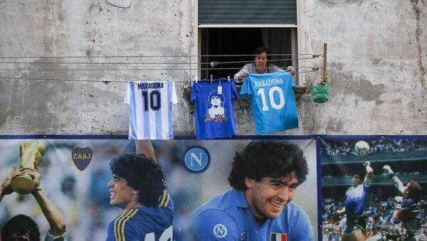 Una donna appende una maglietta con il numero 10 e la scritta Diego Maradonna su una corda in Quartieri Spagnoli di Napoli - Sputnik Italia