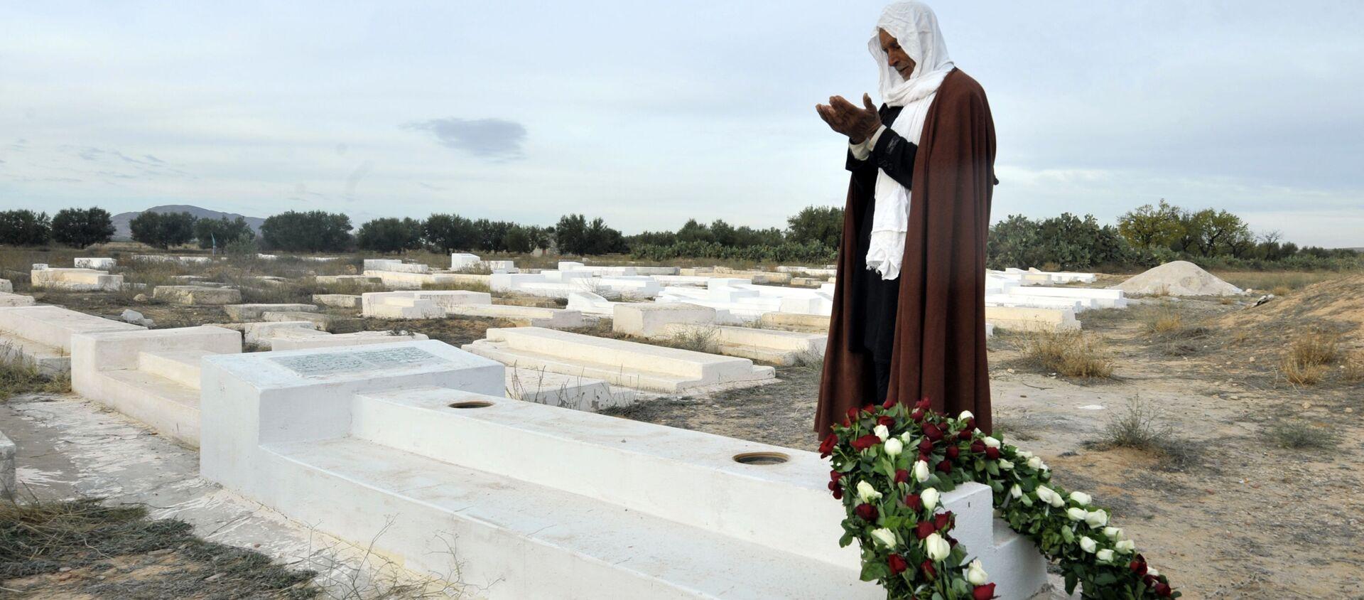 Un uomo prega sulla tomba di Mohammed Bouazizi in Tunisia - Sputnik Italia, 1920, 15.12.2020