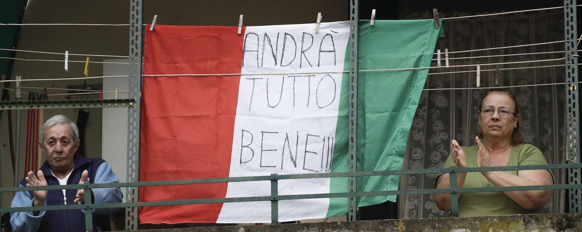 Coppia di anziani sul balcone con la bandiera dell'Italia con la scritta Andrà tutto bene a Roma - Sputnik Italia, 1920, 23.12.2020