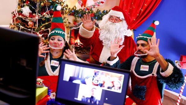Un uomo vestito da Babbo Natale e i suoi assistenti vestiti da elfi chiacchierano con i bambini via Zoom a Roma, Italia - Sputnik Italia