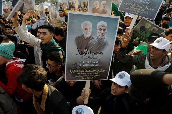 Persone con cartelli durante il primo anniversario della morte del comandante iraniano Qasem Soleimani e del comandante iracheno Abu Mahdi al-Muhandis a Baghdad - Sputnik Italia