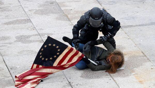 Un agente di polizia arresta un manifestante nel corso delle proteste a sostegno del presidente in carica Donald Trump, Washington, USA. - Sputnik Italia