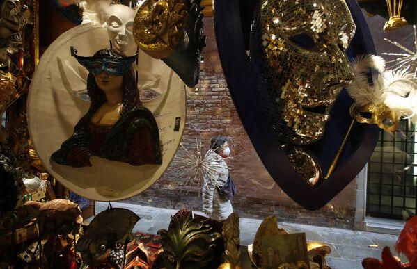 Una donna che indossa una mascherina cammina accanto a un negozio di maschere di carnevale a Venezia, Italia, sabato 30 gennaio 2021. Il carnevale avrebbe dovuto iniziare sabato, ma la pandemia COVID-19 ha reso quella festa annuale impossibile.  - Sputnik Italia