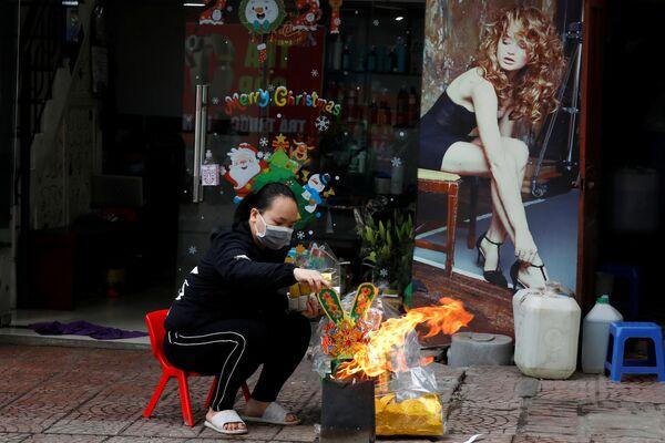Una donna brucia le banconote finte nell'ambito dei festeggiamenti dedicati al Capodanno Lunare in Vietnam.  - Sputnik Italia