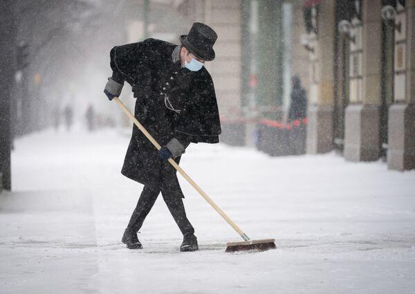 Un dipendente dell'Adlon Hotel pulisce il marciapiede di Paris Square a Berlino - Sputnik Italia