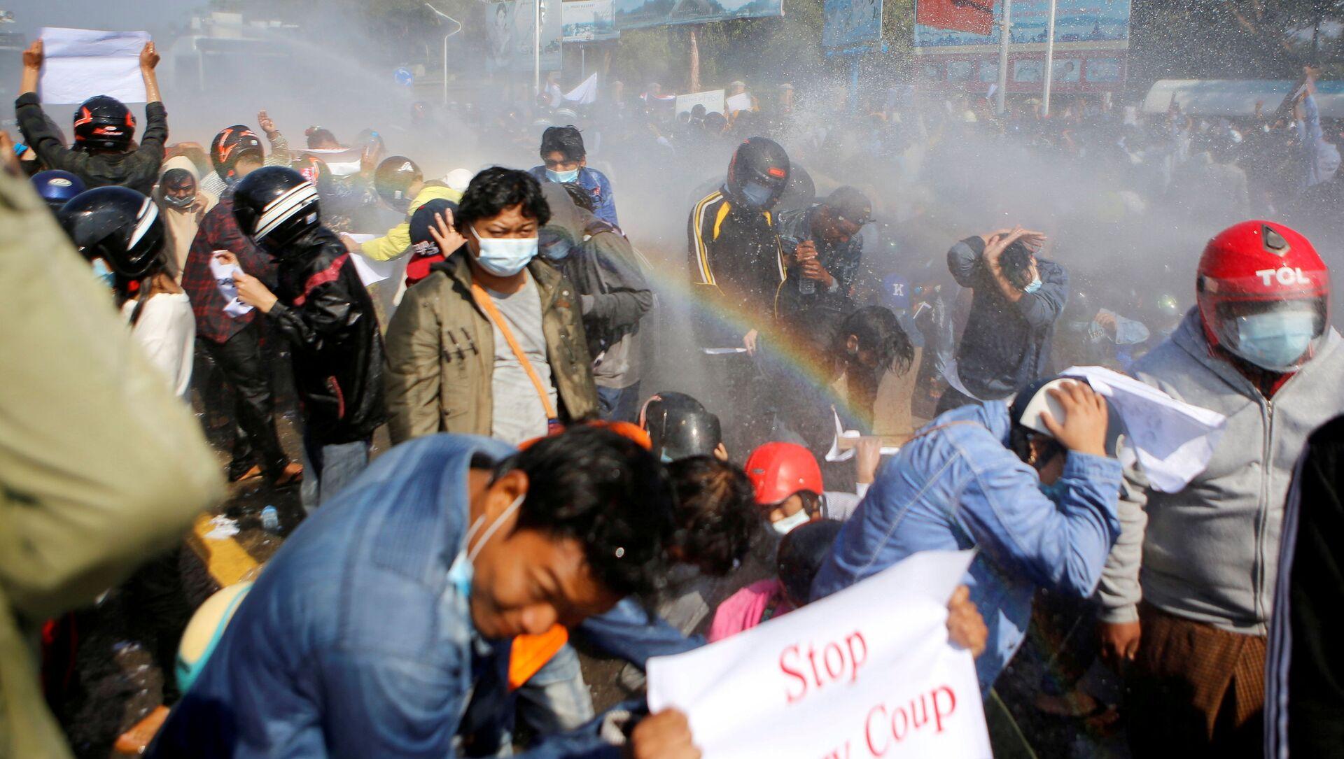 Полиция стреляет из водомета по демонстрантам, выступающим против военного переворота, в Нейпьито, Мьянма - Sputnik Italia, 1920, 28.02.2021