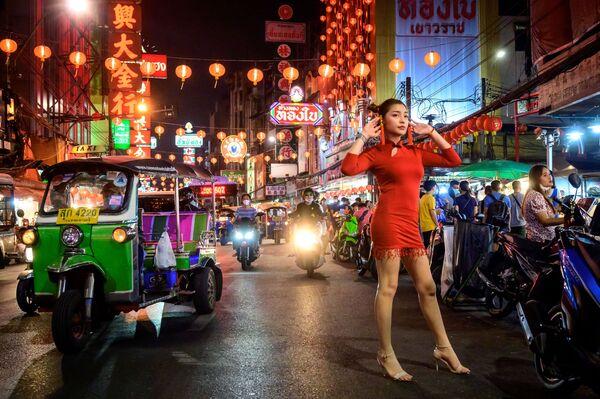 Una ragazza posa per una foto in una strada addobbata per il capodanno lunare nella Chinatown di Bangkok - Sputnik Italia