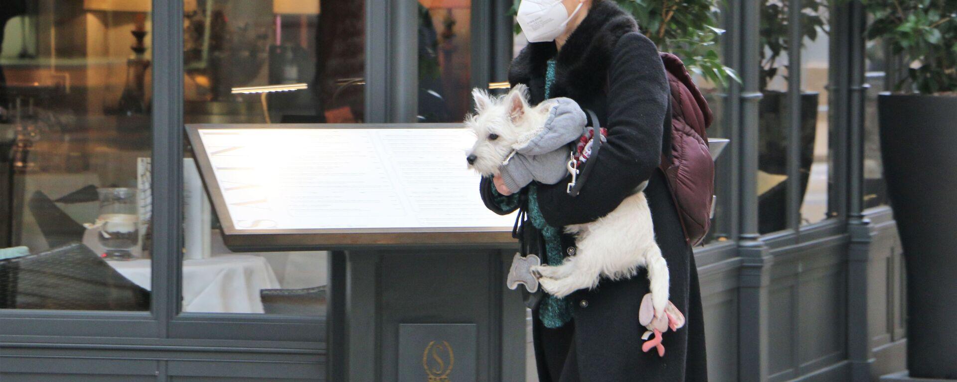 Una donna in una mascherina protettiva con un cane a Milano - Sputnik Italia, 1920, 27.03.2021