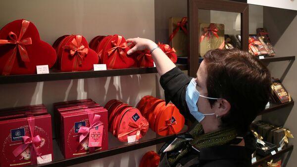 Продавец одного из самых престижных производителей шоколада Бельгии расставляет коробки во время подготовки ко Дню святого Валентина в Брюсселе, Бельгия - Sputnik Italia
