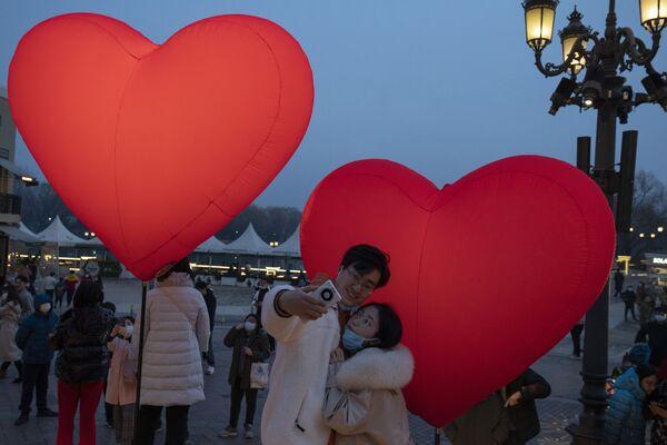 Le persone fanno le foto vicino a palloncini a San Valentino, Pechino - Sputnik Italia