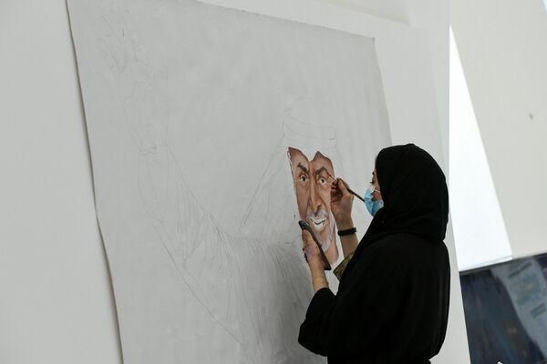 Una donna dipinge un ritratto del principe ereditario Mohammed bin Zayed Al Nahyan alla mostra dell'industria della difesa IDEX-2021 ad Abu Dhabi - Sputnik Italia