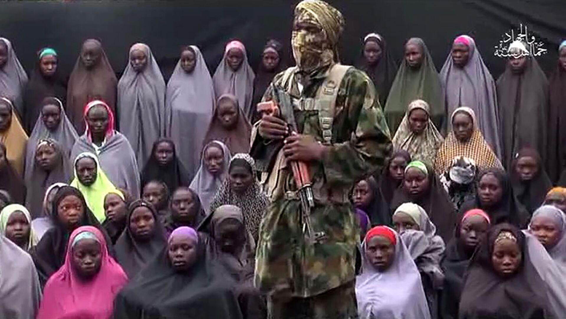 This file photo taken on August 14, 2016 shows a video grab image created on August 14, 2016 and taken from a video released on youtube purportedly by Islamist group Boko Haram showing what is claimed to be one of the groups fighters at an undisclosed location standing in front of girls allegedly kidnapped from Chibok in April 2014. - Sputnik Italia, 1920, 02.03.2021
