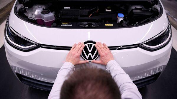 Рабочий устанавливает логотип VW на электромобиле Volkswagen ID.3 на сборочном конвейере автозавода Volkswagen - Sputnik Italia