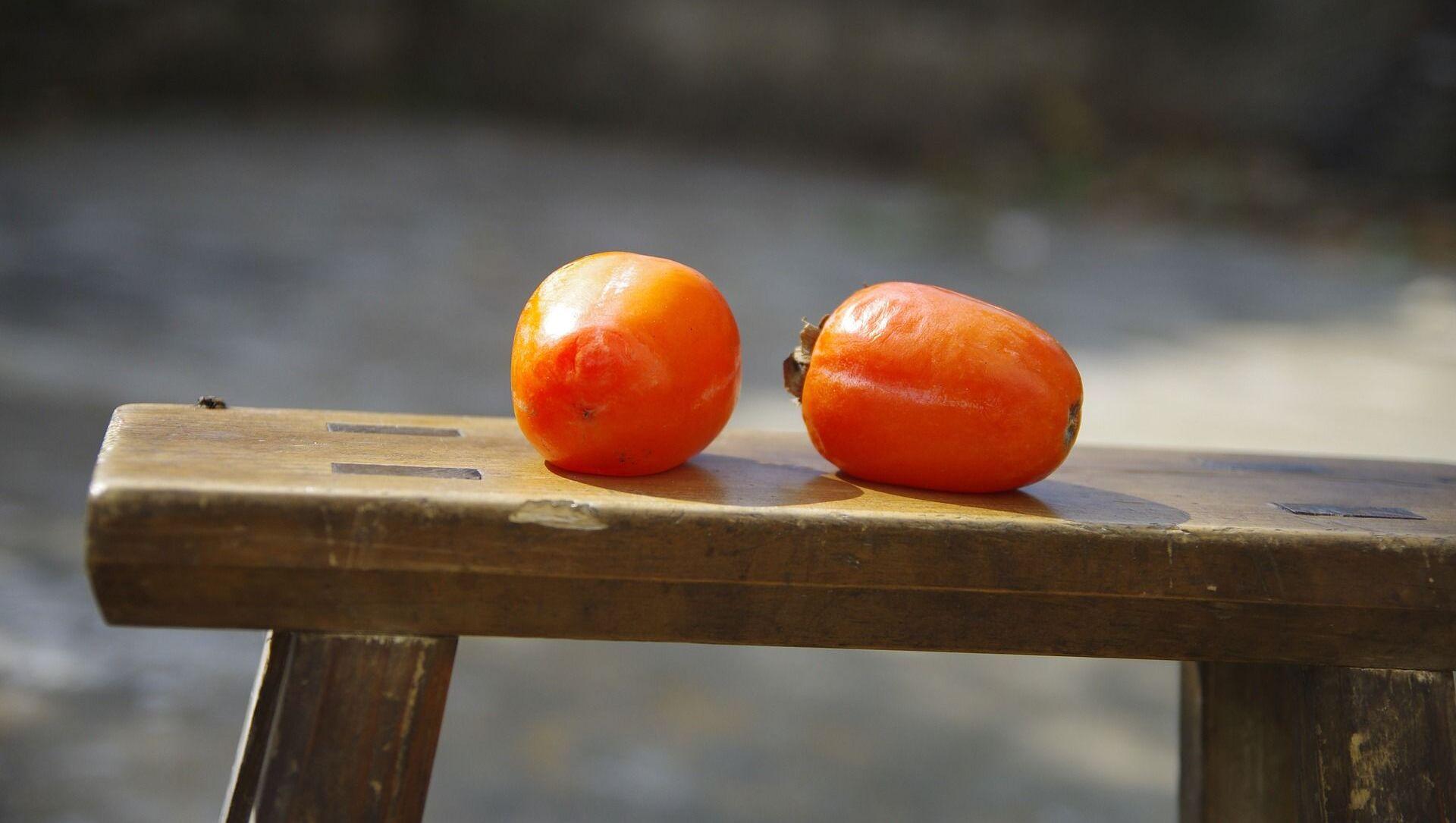 Две спелых хурмы лежат на скамейке - Sputnik Italia, 1920, 05.03.2021