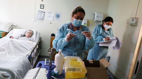 Медицинские работники в доме престарелых в Сантьяго перед вакцинацией от коронавируса пожилой пациентки - Sputnik Italia