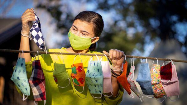 Una ragazza appende le mascherine - Sputnik Italia